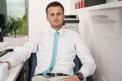 Young Businessman Relaxes Sitting In The Office Stock Image