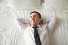 Young businessman relaxing in bed Stock Images