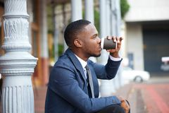 Young businessman relaxing and drinking coffee in the city Royalty Free Stock Photography