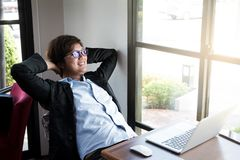 Young businessman relaxing at his desk in coffee shop. Relax,Success Royalty Free Stock Images