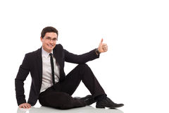 Young businessman relaxing and showing thumb up. Stock Photos