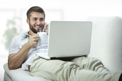 Young businessman relaxing after work. Young businessman with coffee cup and laptop relaxes Stock Images