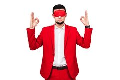 Young businessman relies on luck, fortune. bearded man in a red suit with a red blindfold. Isolated on white stock images