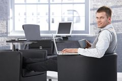 Young businessman resting in armchair with laptop Royalty Free Stock Images