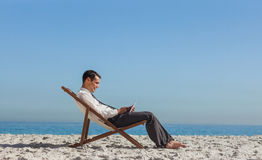 Young businessman resting on his deck chair using his tablet Royalty Free Stock Photo