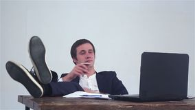 Young businessman is resting, looking at a laptop and drinking coffee. stock footage