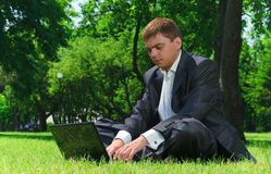 Young businessman resting in a park on the grass Royalty Free Stock Images