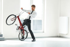 Young Businessman Rides on His Bike at Office. Business People Royalty Free Stock Photos