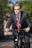 Young businessman riding bicycle on street Royalty Free Stock Images