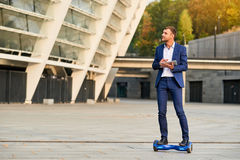 Young businessman riding hoverboard. royalty free stock image