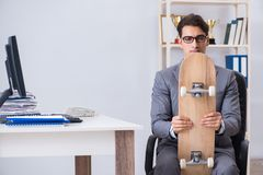 The young businessman riding skate in office during break. Young businessman riding skate in office during break Stock Photo