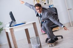 The young businessman riding skate in office during break. Young businessman riding skate in office during break Royalty Free Stock Photography