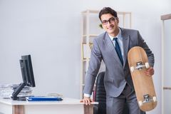 The young businessman riding skate in office during break. Young businessman riding skate in office during break Royalty Free Stock Image