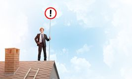 Businessman on house top showing sign with exclamation mark. Mixed media. Young businessman with roadsign in hand standing on brick roof. Mixed media Royalty Free Stock Photo