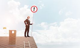Businessman on house top showing sign with exclamation mark. Mixed media. Young businessman with roadsign in hand standing on brick roof. Mixed media Stock Photo