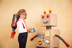 Young businessman with robot. Portrait of young businessman with toy robot in modern loft office. Success, creative and innovation technology concept. Copy space Royalty Free Stock Photography