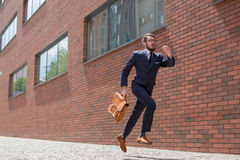 Young businessman running in a city street Royalty Free Stock Photography
