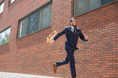 Young businessman running in a city street Stock Photos