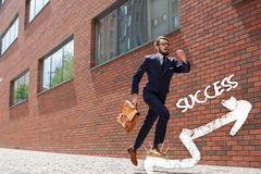 Young businessman running in a city street. Young businessman with a briefcase and glasses running in a city street on a background of red brick wall. The Royalty Free Stock Photo