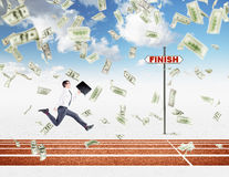 A young businessman running forward with a black folder in hand approaching the finish line, dollars falling from above. Stock Image