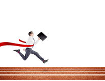 A young businessman running forward on track with a black folder in hand crossing the red finish line. Royalty Free Stock Photography