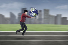 Young businessman running with globe Stock Photo