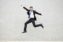 Young businessman running and jumping stock photography