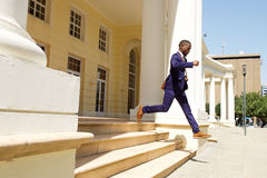 Young businessman running out of a building royalty free stock photography