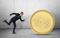 Young businessman running to catch a big golden coin Stock Photo