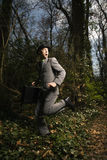 Young Businessman Running In Woods. Young businessman fearfully runs through the woods while looking behind. Vertical shot royalty free stock photography