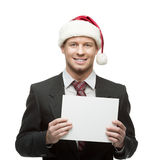 Young businessman in santa hat holding sign Royalty Free Stock Photos
