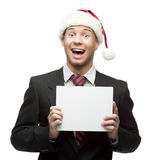Young businessman in santa hat holding sign. Young smiling caucasian businessman in black suit and santa hat holding sign isolated on white Stock Photography