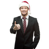 Young businessman in santa hat showing thumbs up Royalty Free Stock Image