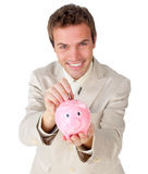 Young businessman saving money in a piggy-bank Royalty Free Stock Photography