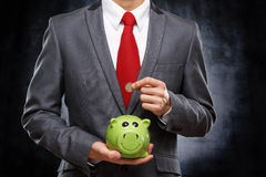 Young businessman saving money. In piggy bank on dark background Stock Photos