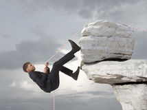 Young businessman scaling a rock Stock Image