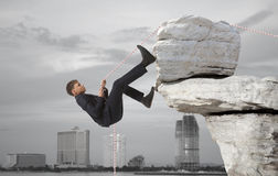 Young businessman scaling a rock Royalty Free Stock Photos