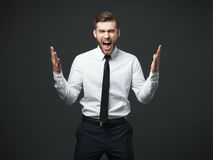 Young businessman screaming at camera isolated. Royalty Free Stock Images