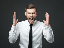 Young businessman screaming at camera isolated. Stock Photography