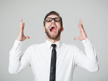 Young businessman screaming -  isolated on gray background. Royalty Free Stock Photo