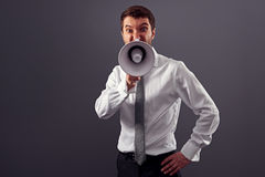 Young businessman screaming in megaphone Stock Images