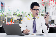 Young businessman screaming at mobilephone Royalty Free Stock Photos