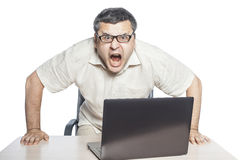 Young businessman screaming. Businessman sitting at laptop and shouting, crisis and stress at work Royalty Free Stock Photography