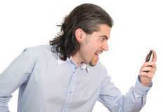 Young businessman screams on his cell phone. Young dark haired caucasian man in light blue striped shirt screaming angrily at his mobile phone isolated on white Royalty Free Stock Photography