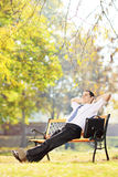 Young businessman seated on a bench relaxing in a park Royalty Free Stock Images
