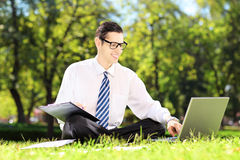 Young businessman seated on a grass working on laptop in a park Stock Photo