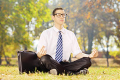 Young businessman seated on a green grass meditating in a park Stock Photography