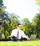 Young businessman seated working on a laptop and writing down no Stock Image
