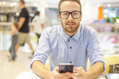 Young Businessman seating on table in restoran and use mobile de. Smiling Businessman with electronic device on hand, blurred background of indor shopping mall Stock Photo