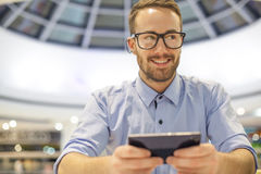 Young Businessman seating on table in restoran and use mobile de. Smiling Businessman with electronic device on hand, blurred background of indor shopping mall Royalty Free Stock Photography